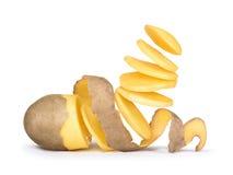 Los pedazos de patata que caían en el aire de las patatas pelaron el potatoe Fotografía de archivo libre de regalías