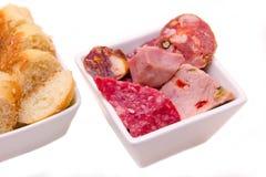 Los pedazos de salami y las rebanadas de pan en cuencos se cierran Imágenes de archivo libres de regalías