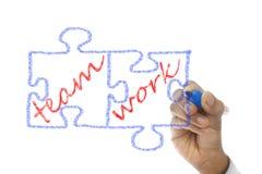 Los pedazos del rompecabezas escritos Team Work se dibujan a bordo Foto de archivo libre de regalías