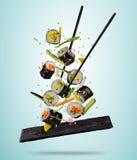 Los pedazos del sushi del vuelo sirvieron en la placa, separada en backgr coloreado Fotografía de archivo libre de regalías