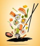 Los pedazos del sushi del vuelo sirvieron en la placa, separada en fondo coloreado Imagen de archivo libre de regalías
