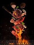 Los pedazos del vuelo de carne de la carne de vaca juntan las piezas en la hamburguesa de la parrilla imagen de archivo