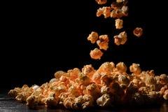 Los pedazos mullidos de palomitas caen en la cámara lenta contra un fondo negro Foto de archivo libre de regalías
