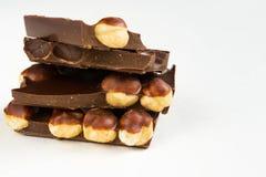 Los pedazos oscuros del chocolate de la avellana se elevan en el fondo blanco imagen de archivo