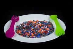 Los pedazos plásticos multicolores machacados en la placa blanca y cuchara y lila verdes bifurcan Fotografía de archivo libre de regalías