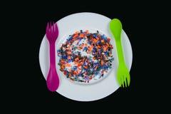 Los pedazos plásticos multicolores machacados en la placa blanca y cuchara y lila verdes bifurcan Fotos de archivo