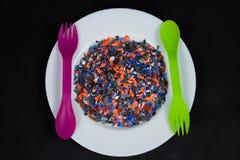 Los pedazos plásticos multicolores machacados en la placa blanca y cuchara y lila verdes bifurcan Fotografía de archivo