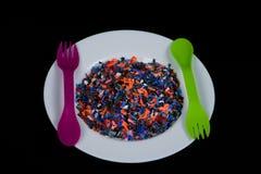 Los pedazos plásticos multicolores machacados en la placa blanca y cuchara y lila verdes bifurcan Fotos de archivo libres de regalías