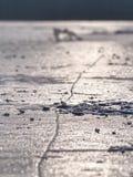Los pedazos quebrados de hielo grueso sobre el lago congelado brillan en sol foto de archivo