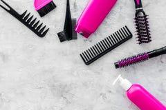 Los peines, los cepillos y el espray rosados para el peluquero funcionan en la maqueta de piedra de la opinión superior del fondo Foto de archivo libre de regalías