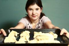 Los pelos oscuros largos de la muchacha preparan las empanadas con para cortar manzanas Foto de archivo