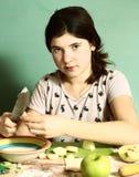 Los pelos oscuros largos de la muchacha preparan las empanadas con para cortar manzanas Fotografía de archivo