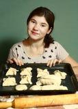 Los pelos oscuros largos de la muchacha preparan las empanadas con para cortar manzanas Foto de archivo libre de regalías