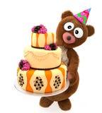 Los peluches del oso con los ojos grandes sostienen la torta dulce del cumpleaños Imagen de archivo