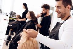 Los peluqueros hacen el corte de pelo para las mujeres de diversas categorías de la edad en salón de belleza fotografía de archivo libre de regalías