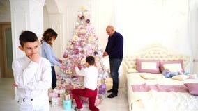 Los pensamientos del ` s de los niños del muchacho sobre cómo conseguir desearon el regalo o la enhorabuena para los padres en do almacen de metraje de vídeo