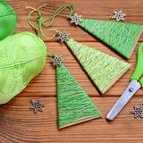 Los pequeños árboles de navidad se hacen del cartón, hilo de algodón y se adornan con los pequeños copos de nieve del metal Artes Fotografía de archivo