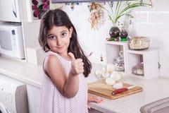 Los pequeños 7 años de Oriente Medio hermosos de la muchacha están trabajando con el cuchillo y la cebolla en la cocina blanca Ti Imagenes de archivo