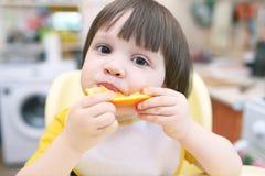 Los pequeños 2 años preciosos de niño comen la naranja Foto de archivo libre de regalías