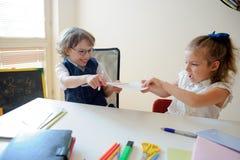 Los pequeños alumnos divertidos se sientan en un escritorio Imagen de archivo