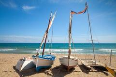 Los pequeños barcos de navegación ponen en la playa arenosa en la ciudad de Calafell Imágenes de archivo libres de regalías
