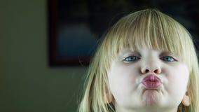 Los pequeños besos lindos de la muchacha en la cámara almacen de metraje de vídeo