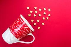 Los pequeños corazones de madera vuelan de una taza roja con un amor de la inscripción El día de tarjeta del día de San Valentín, foto de archivo libre de regalías