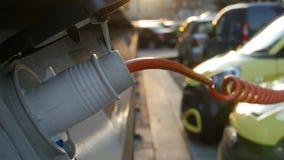 Los pequeños electro coches amarillos están cargando en la estación de la calle Primer almacen de video