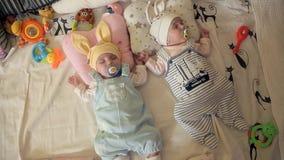 Los pequeños gemelos del bebé están rápidamente dormidos en el parque de niños, chupando el pacificador del soother almacen de metraje de vídeo