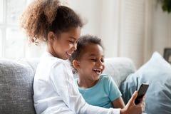 Los pequeños hermanos negros de risa se divierten usando smartphone imagen de archivo libre de regalías