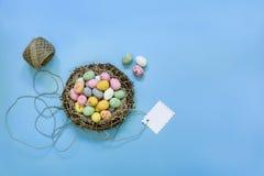 Los pequeños huevos de chocolate pintados en una cesta jerarquizan con la etiqueta en un fondo azul Foto de archivo