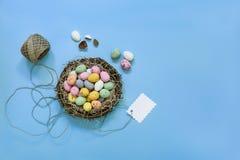 Los pequeños huevos de chocolate pintados en una cesta jerarquizan con la etiqueta en un fondo azul Fotografía de archivo libre de regalías