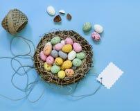 Los pequeños huevos de chocolate pintados en una cesta jerarquizan con la etiqueta en un fondo azul Imagen de archivo
