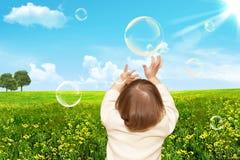 Los pequeños juegos de la muchacha con las burbujas de jabón Imágenes de archivo libres de regalías