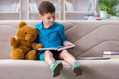 Los pequeños libros de lectura del muchacho en casa imagenes de archivo