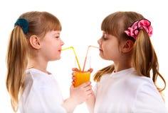 Los pequeños muchacha-gemelos beben el zumo de naranja Fotos de archivo libres de regalías