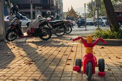Los pequeños niños árbol-rodaron la bicicleta que se colocaba delante de las motos y de las vespas imagen de archivo