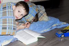 Los pequeños niños están leyendo un libro debajo de la manta El muchacho juega debajo de la manta en casa antes de hora de acosta foto de archivo libre de regalías