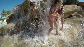 Los pequeños niños hermosos se colocan debajo de los chorros de agua almacen de video
