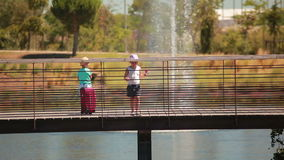 Los pequeños niños preciosos sostienen las manos y el puente cruzado almacen de video
