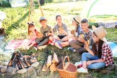 Los pequeños niños que comen los bocadillos acercan a la hoguera fotos de archivo libres de regalías