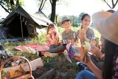 Los pequeños niños que comen los bocadillos acercan a la hoguera imagen de archivo libre de regalías