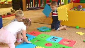 Los pequeños niños recogen el rompecabezas con alfabeto metrajes