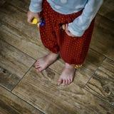 Los pequeños pies desnudos del bebé se colocan en el suelo de baldosas de madera Fotografía de archivo libre de regalías