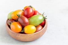 Los pequeños tomates de cereza coloridos en el cuenco de madera, horizontal, copian el espacio Fotografía de archivo libre de regalías