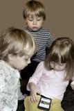 Los pequeños tríos rubios curiosos lindos miran historietas en smartphone imagen de archivo