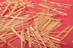 Los peque?os palillos de madera se mezclan en un fondo rojo imágenes de archivo libres de regalías