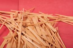 Los peque?os palillos de madera se mezclan en un fondo rojo imagen de archivo libre de regalías