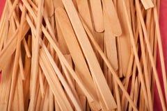 Los peque?os palillos de madera se mezclan en un fondo rojo foto de archivo