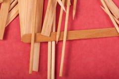 Los peque?os palillos de madera se mezclan en un fondo rojo fotos de archivo libres de regalías